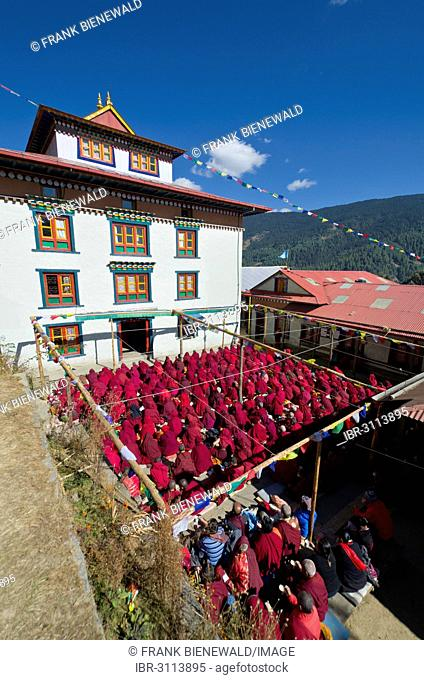 Many nuns wearing red cloths listening the teachings of Taklung Tsetrul Rinpoche in the backyard of Junbesi Gompa