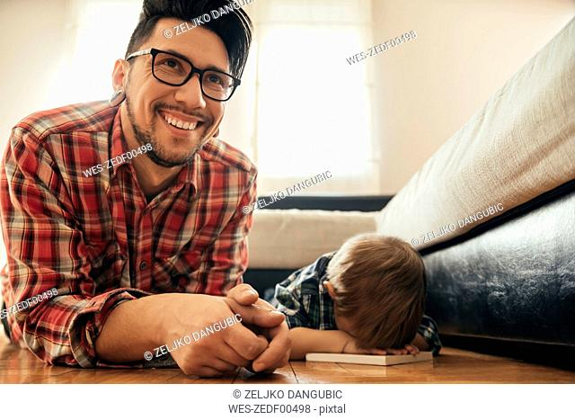 Father and son lying on the floor with a book