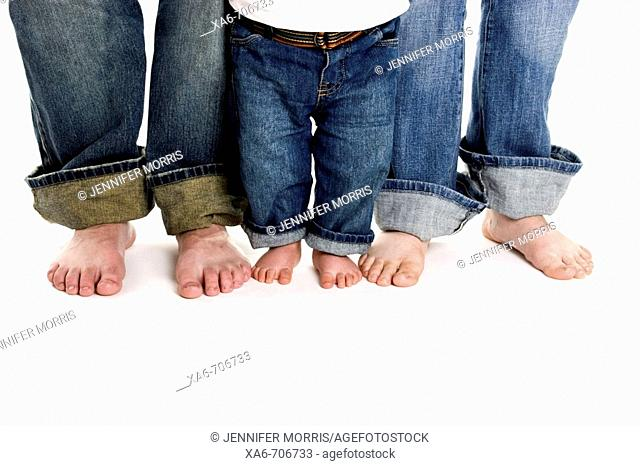 A family of three, mother, father and toddler son, stand on a white background wearing jeans. Only their legs and bare feet are shown