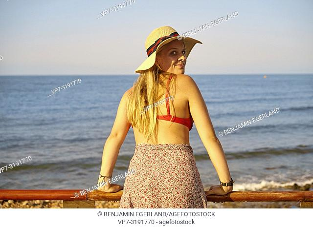 Woman leaning on handrailing next to beach, Stalida, Crete, Greece