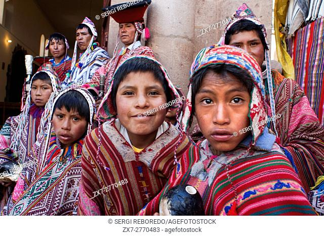 Sacred Valley, Pisac, Peru. The mountain people dressed in traditional costumes at the door of the church of Pisac Sunday market day. Pisac