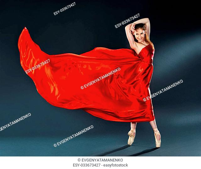 beautiful dancer ballerina dancing a long theatrical red silk dress flying and in pointe