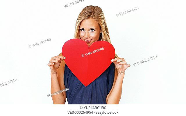 A gorgeous young woman holding a red heart and showing it to you isolated on white