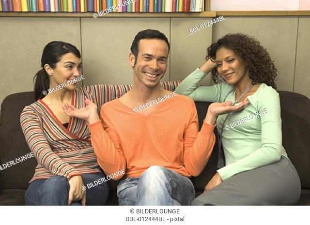 man in orange sweater laughing with his friends