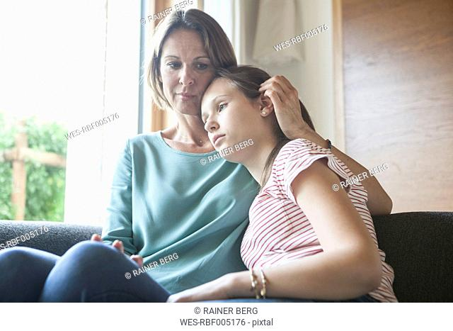 Mother comforting daughter sitting on sofa