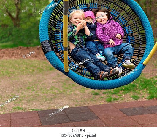 Young children on playground swing, portrait