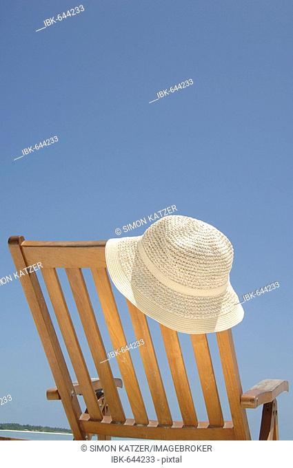 Sun hat placed on a wooden deck chair, Diffushi Island, Holiday Island, Southern Ari Atoll, Maldives, Indian Ocean