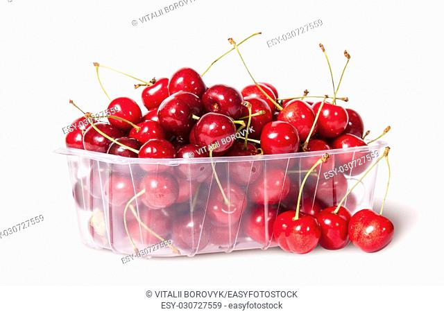 Red sweet cherries in plastic tray rotated and three near isolated on white background