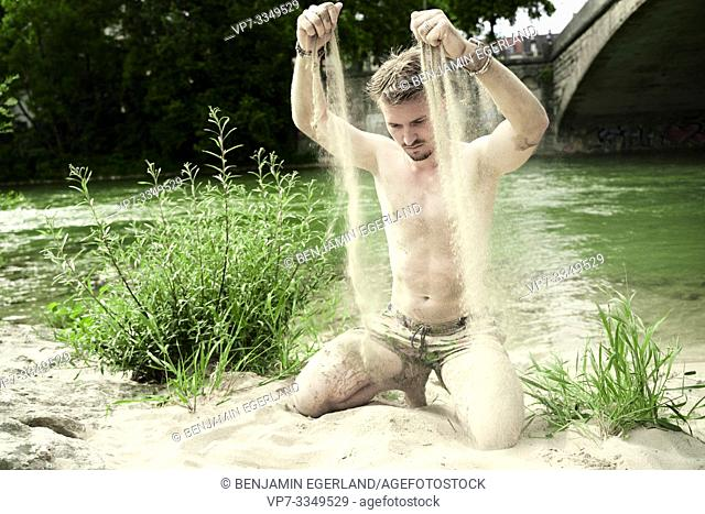 man playing with sand at river Isar, in Munich, Germany