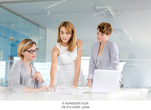 Female architects discussing blueprint at laptop in conference room meeting