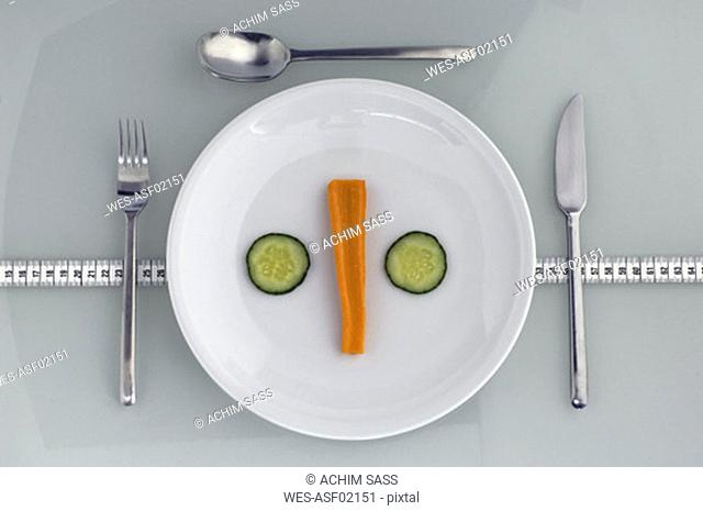 Plate with carrot and cucumber on measuring tape, close-up