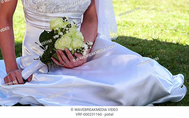 Smiling bride sitting on the grass on her wedding day