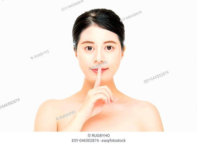Beautiful woman with bare shoulders making a shushing gesture holding her index finger to her lips as she asks for silence or secrecy for a surprise