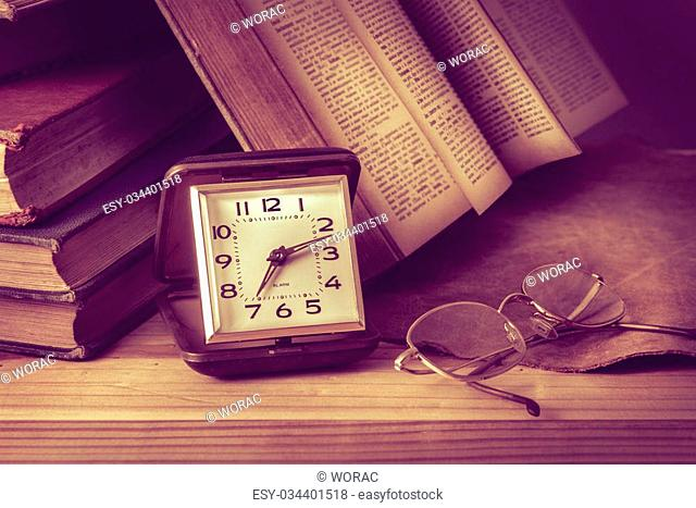 An antique pocket watch, glasses and books come together in this vintage still life