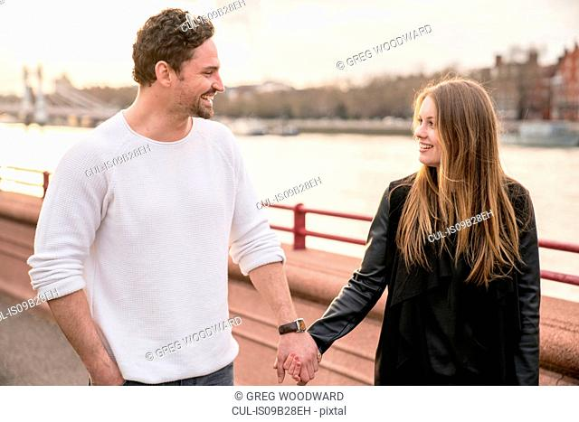 Romantic couple strolling on waterfront, Battersea Park, London, UK