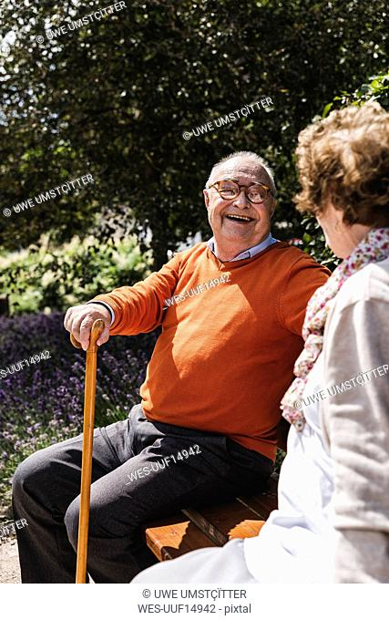 Senior couple sitting on bench in a park, talking