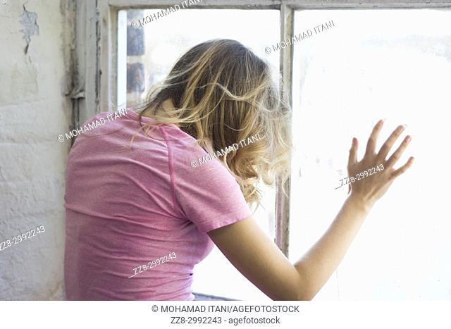 Rear view of a blond woman standing by the window hands touching the glass