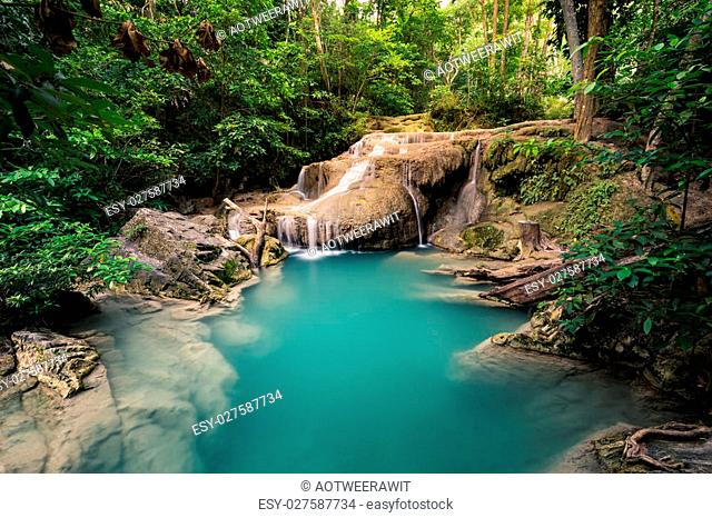 Waterfall with stones and clean green water with nobody and the forest in the background