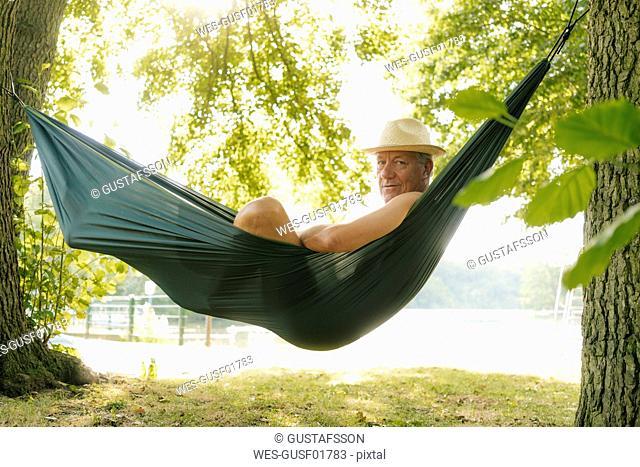 Senior man wearing straw hat relaxing in hammock at lakeshore