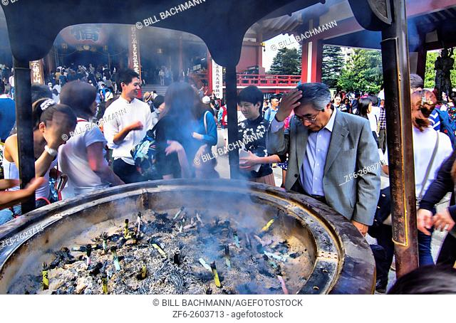 Tokyo Japan Sensoji Temple with crowds at Tokyo's oldest temple and smoke for religion Buddhists wiping smoke on faces to pray