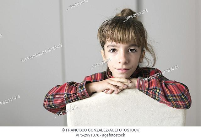Portrait of a 10 year old girl sitting on a chair. Horizontal shot