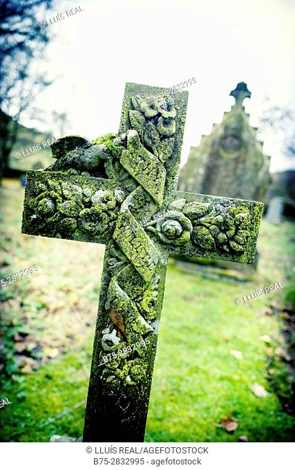 Close-up of a funerary sculpture, cross carved with flowers in a cemetery. Hubberholme, Skipton, Yorkshire Dales, North Yorkshire, England, UK