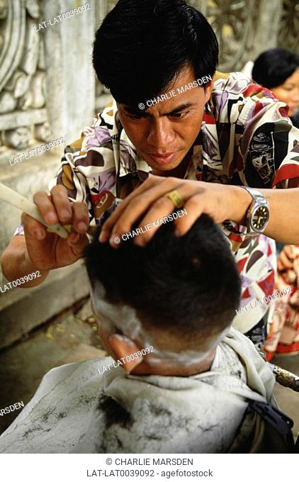 Barbers frequently conduct their business on the street,shaving customers sitting in traditional raised chairs,using cut throat hand held razors
