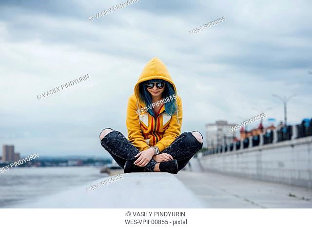 Young woman with dyed blue hair sitting on a wall wearing fashionable hooded jacket