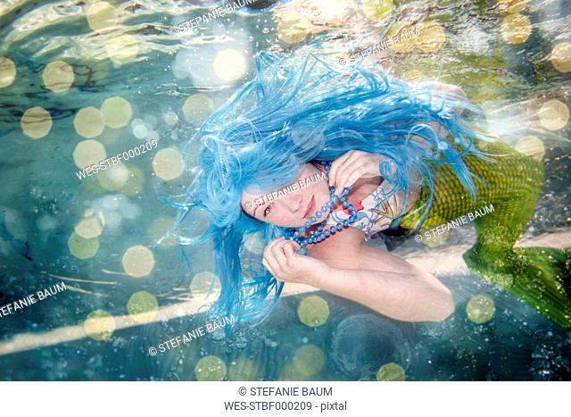 Young woman in the disguise of Arielle, the little mermaid, blue hair, underwater