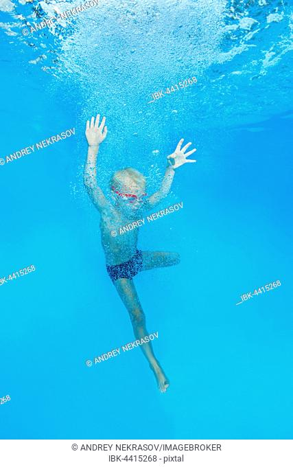 Little boy with swimming goggles, jumping into swimming pool, underwater, Ukraine