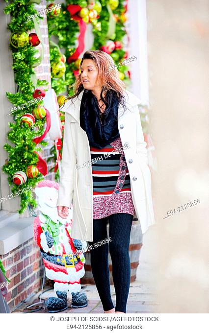 A 27 year old brunette woman shopping on a small town street with holiday decorations