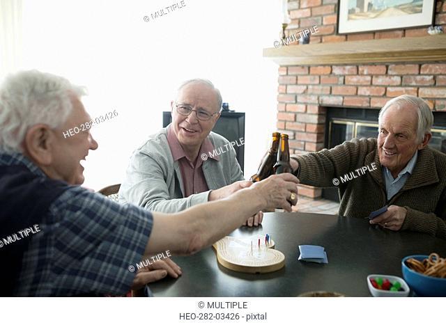 Senior men playing cribbage and toasting beer bottles