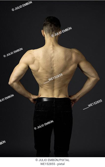Young guy in jeans and shirtless poses in the studio