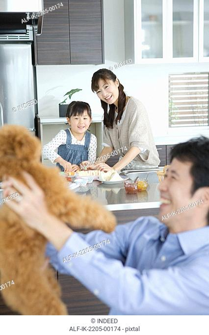 Father holding dog with family in background