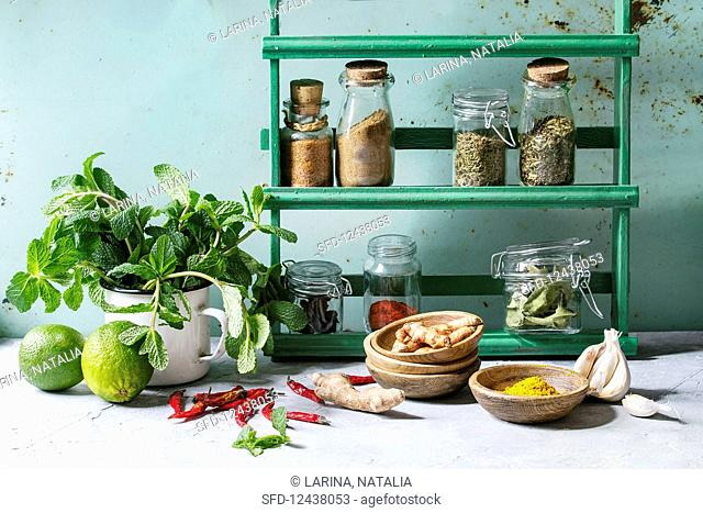 Kitchen table with variety of spices, fresh mint and limes