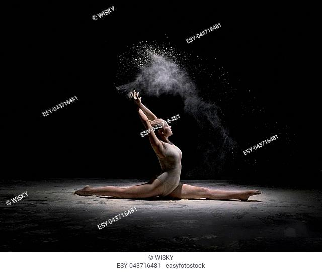 Young flexible dancer performing on dark stage in cloud of white powder, in motion