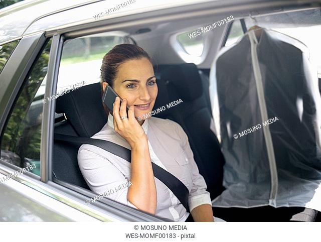 Businesswoman on the phone sitting on backseat of a car