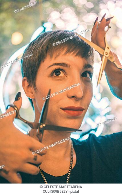 Portrait of young woman framing face with two pairs of open scissors