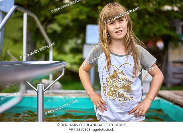 Confident young girl looking at camera while standing in water