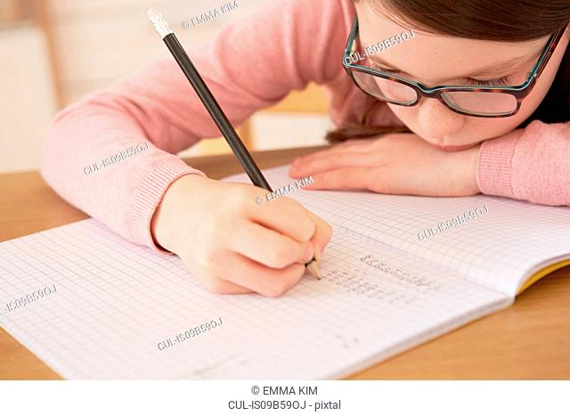 Close up of girl doing homework at table