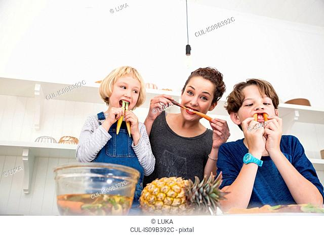 Young woman, boy and girl in kitchen, fooling around, using carrots as false teeth