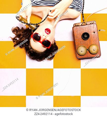 Classic pin-up beauty decision making while conversing on a wooden box telephone on yellow and white retro tiles. Indecisive musings