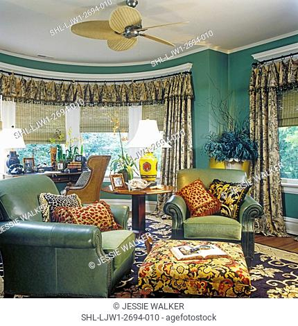 WINDOW TREATMENTS: Semi-circle of bay windows, rich fabric drapes with valance hang from a custom made curved iron rod, sea-grass shades