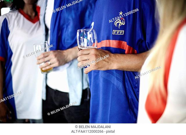 French football supporters drinking beer in bar, cropped