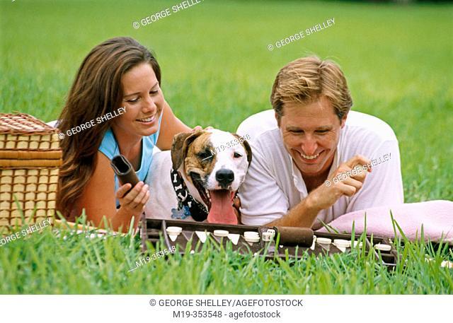 Couple with dog playing backgammon