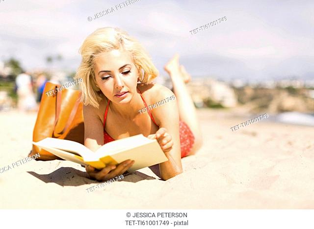 Portrait of blond woman reading book on beach
