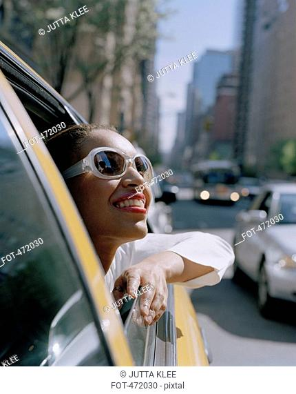 A woman looking out of a taxi window, New York City, USA