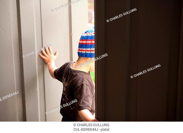 Young boy walking through doorway