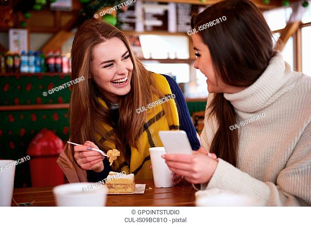 Young women smiling over text message on mobile phone