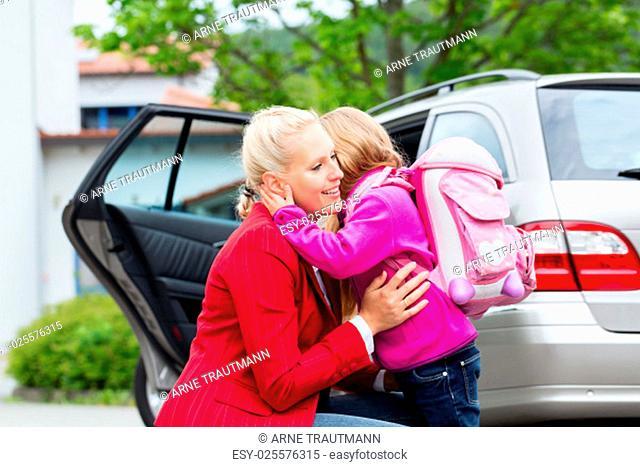 Mutter umarmt Tochter beim Bringen zur Schule